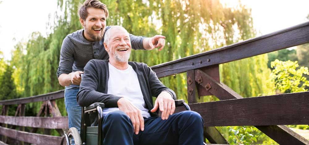 Poika työntää isäänsä pyörätuolissa